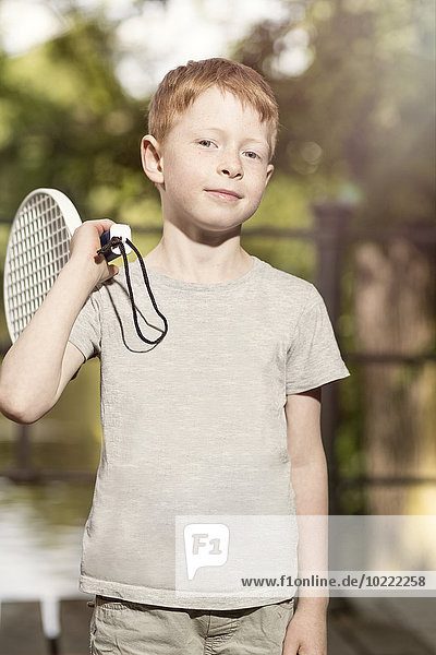 Portrait of little boy with tennis racket on his shoulder