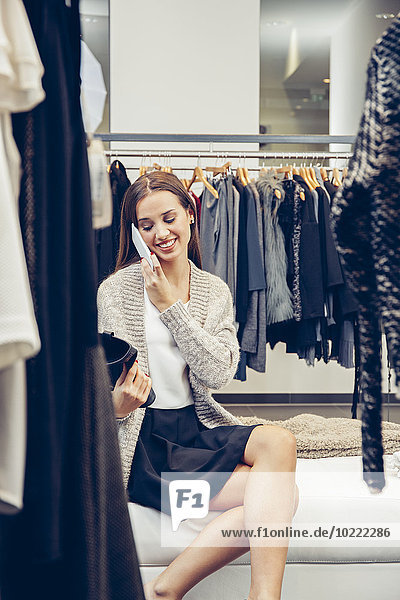 Smiling young woman on cell phone in a boutique