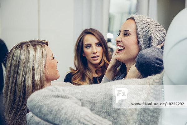 Fröhliche junge Frau mit Wollmütze in einer Boutique mit zwei Frauen