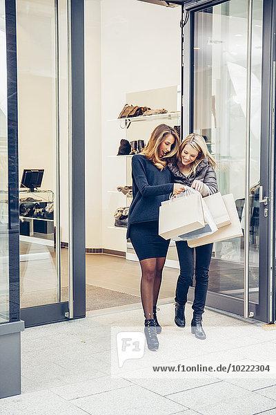 Zwei glückliche junge Frauen mit Einkaufstaschen  die eine Boutique verlassen.