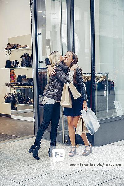 Zwei glückliche junge Frauen mit Einkaufstaschen  die sich vor einem Laden umarmen.