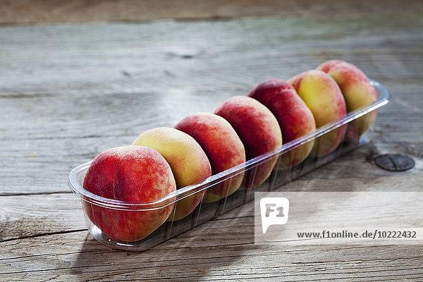 Plastikdose mit Donutpfirsichen auf Holz