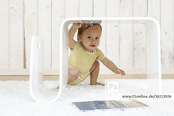 Baby Girl hockt unter dem modernen Beistelltisch