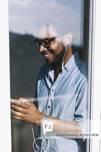 Lächelnder junger Mann hinter der Fensterscheibe hört Musik vom Smartphone