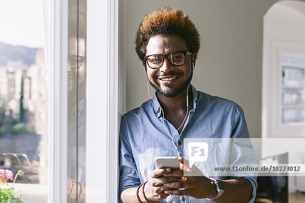 Portrait of smiling young man listening to music from smartphone