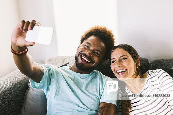 Glückliches junges Paar fotografiert sich selbst mit dem Smartphone