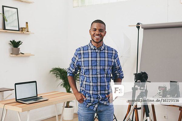 Portrait of smiling young man in his photographic studio