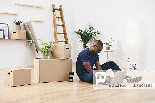 Junger Mann sitzt neben Pappkartons in seiner neuen Wohnung mit Laptop