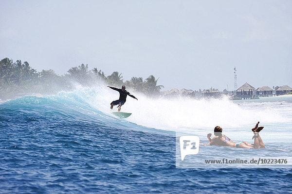Malediven  Süd Male Atoll  Mann beim Surfen  während die Frau auf ihrem Surfbrett liegt und ihn beobachtet.