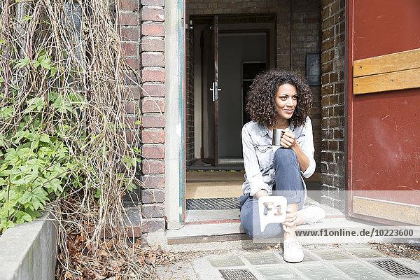 Entschlossene junge Frau auf der Türschwelle sitzend