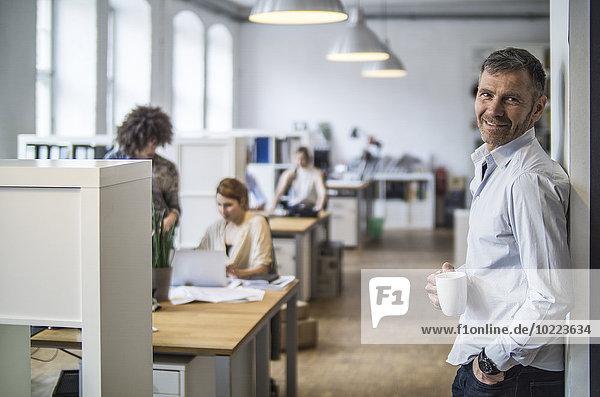 Lächelnder Mann im Büro mit Kollegen im Hintergrund