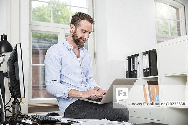 Lächelnder junger Mann im Büro sitzend auf dem Schreibtisch mit Laptop