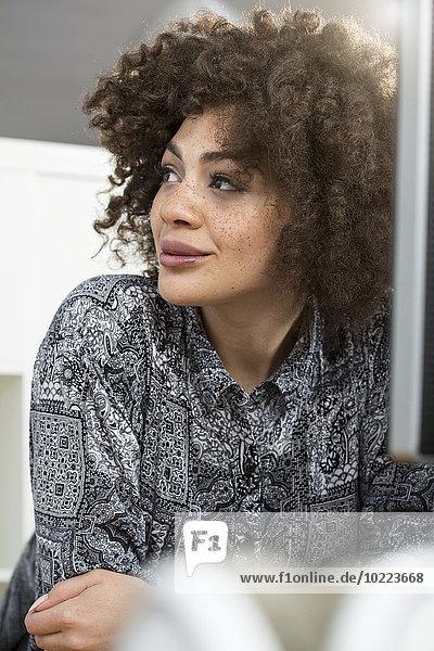 Lächelnde junge Frau im Büro am Schreibtisch schaut seitwärts