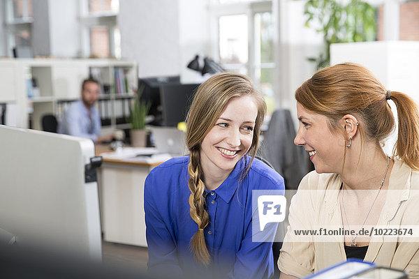 Zwei lächelnde Frauen im Büro  die sich gegenseitig anschauen