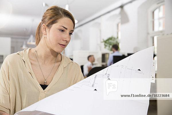 Frau im Büro schaut sich den Plan an