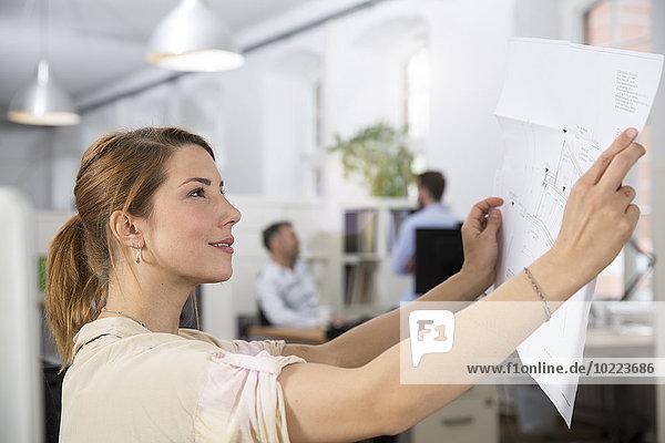 Lächelnde Frau im Büro mit Blick auf den Plan