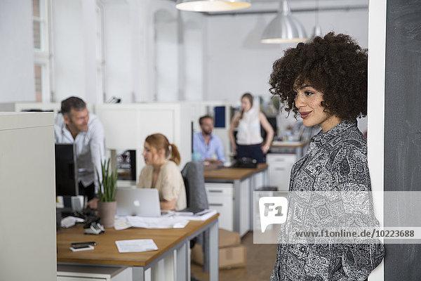 Lächelnde Frau im Büro mit Kollegen im Hintergrund