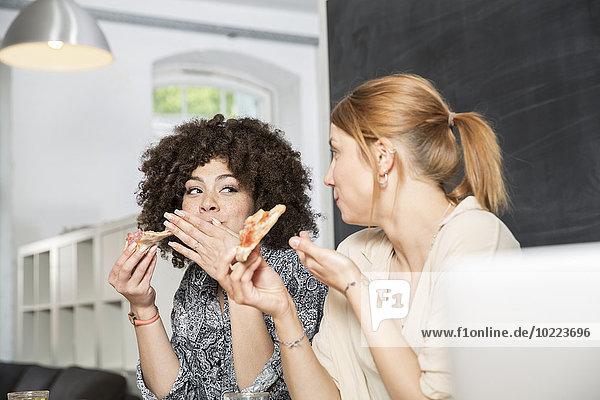 Zwei Kollegen im Büro beim Pizzaessen