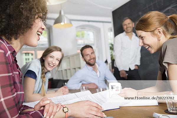 Zufriedene Kollegen im Büro mit einer Besprechung