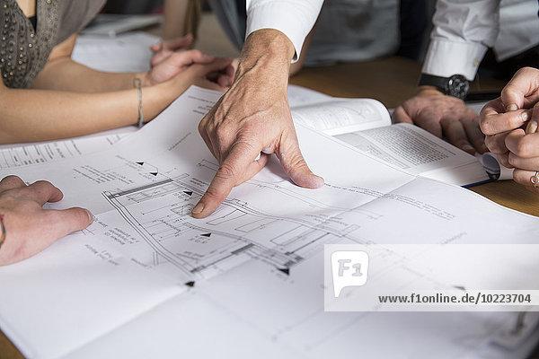 Hand zeigt auf den Bauplan