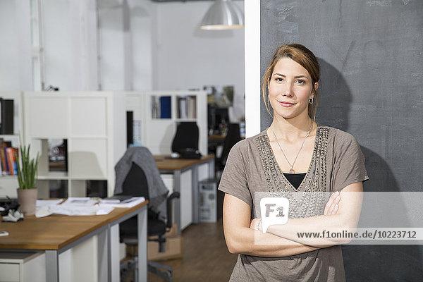 Lächelnde junge Frau an der Tafel im Büro stehend