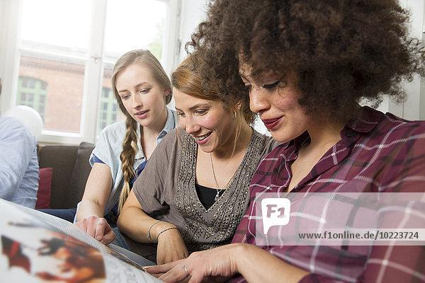 Drei junge Frauen auf der Couch teilen sich das Magazin