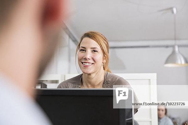 Porträt einer lächelnden jungen Frau mit Kollegen im Amt
