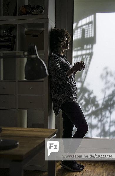 Junge Frau mit Tasse Kaffee am Schrank gelehnt