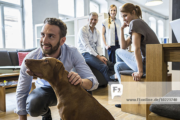 Kollegen mit Hund im Büro
