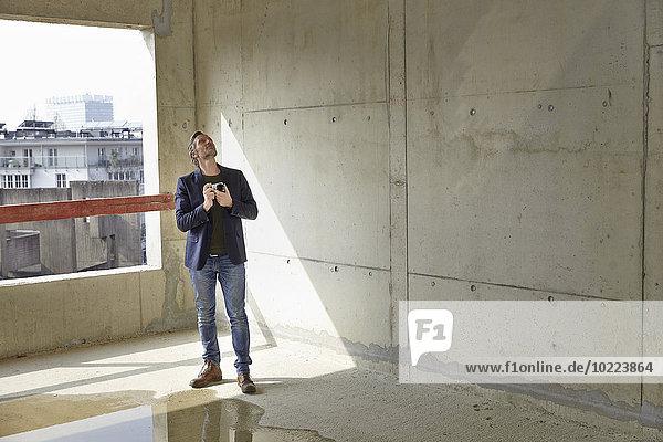 Mann mit Kamera auf der Baustelle im Rohbau