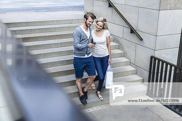 Deutschland  Köln  junges Paar schaut auf das Smartphone und geht die Treppe hinunter