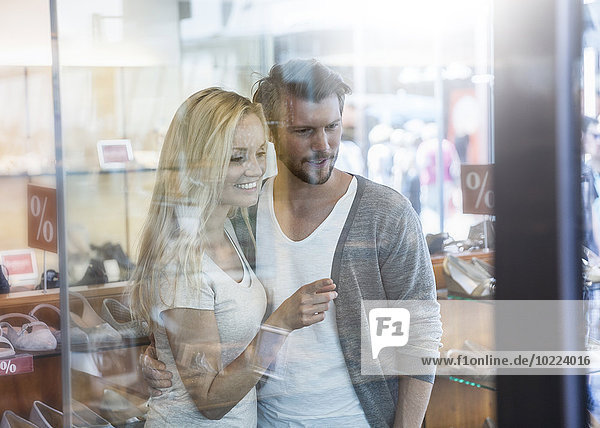 Porträt eines lächelnden jungen Paares beim Einkaufsbummel