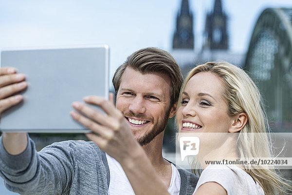 Deutschland  Köln  Porträt eines lächelnden jungen Paares  das einen Selfie mit digitalem Tablett nimmt.
