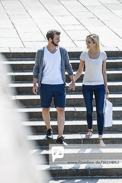 Deutschland  Köln  glückliches junges Paar  das die Treppe hinuntergeht