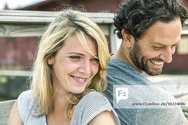 Lächelndes Paar im Freien Rücken an Rücken