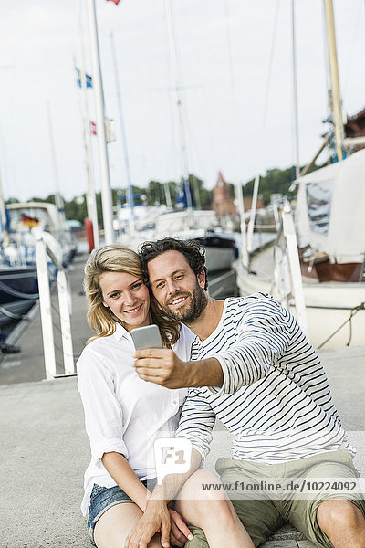 Deutschland  Lübeck  lächelndes Paar im Yachthafen bei einem Selfie