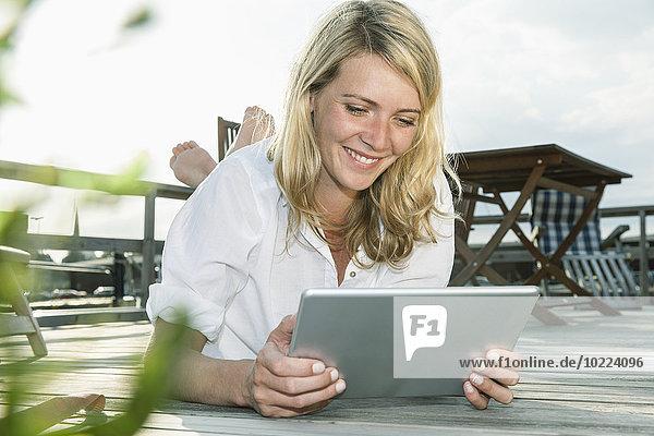 Lächelnde junge Frau entspannt an Deck mit digitalem Tablett