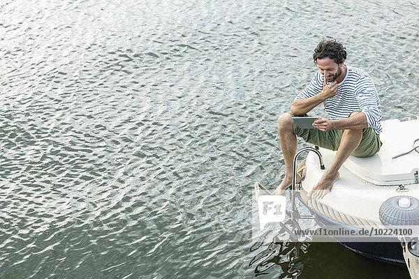 Lächelnder Mann auf dem Boot mit digitalem Tablett