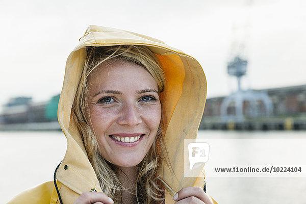 Deutschland  Lübeck  Porträt einer jungen Frau im Regenmantel am Wasser