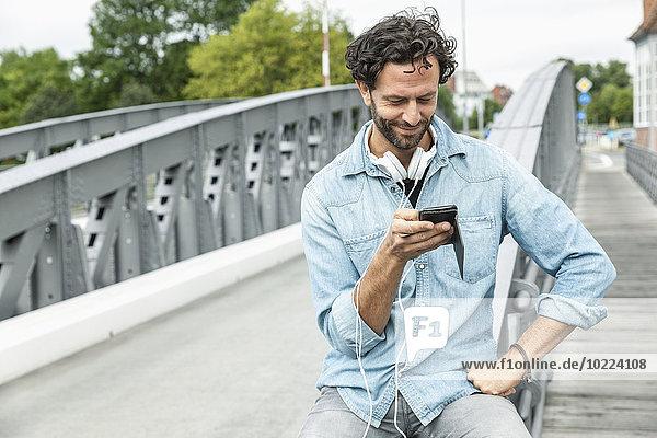 Lächelnder Mann auf einer Brücke mit Blick auf das Handy