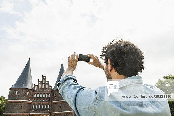 Deutschland  Lübeck  Mann fotografiert vor dem Holstentor