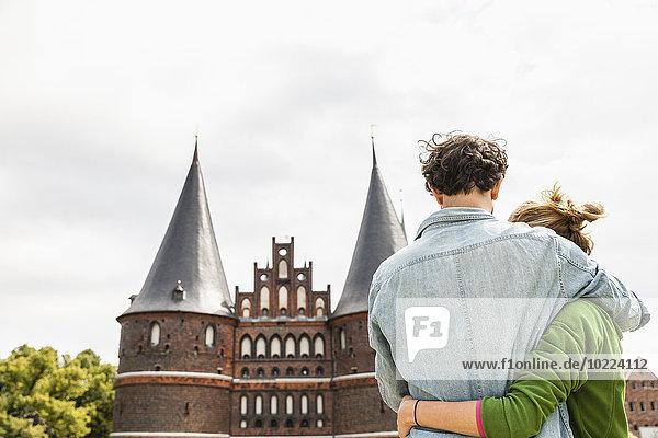 Deutschland  Lübeck  Paar vor dem Holstentor umarmt