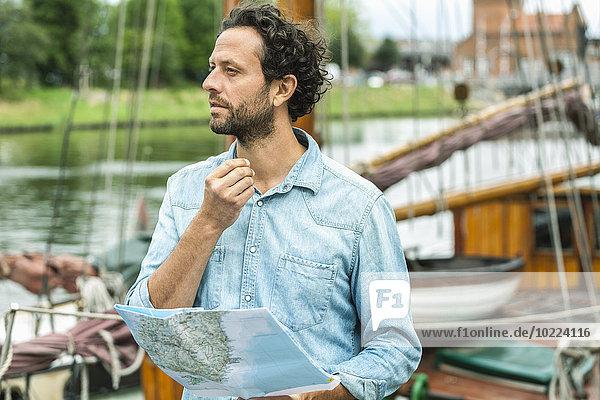 Deutschland  Lübeck  Mann an der Anlegestelle mit Landkarte