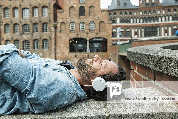 Deutschland  Lübeck  Mann mit Kopfhörern entspannt in der Stadt