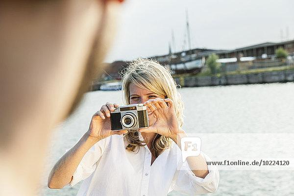 Deutschland  Lübeck  Frau beim Fotografieren am Wasser