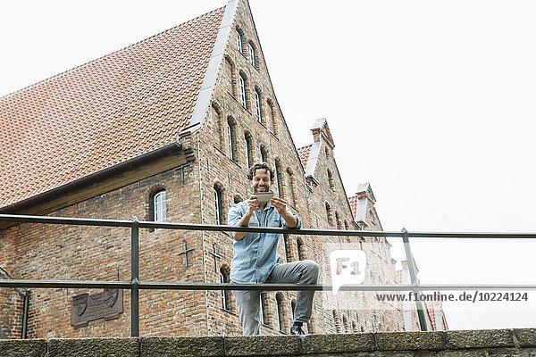 Deutschland  Lübeck  Mann mit Smartphone in der Stadt
