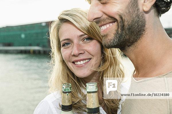 Glückliches Paar beim Biertrinken am Wasser