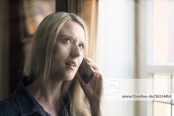 Portrait einer blonden Frau beim Telefonieren mit dem Smartphone