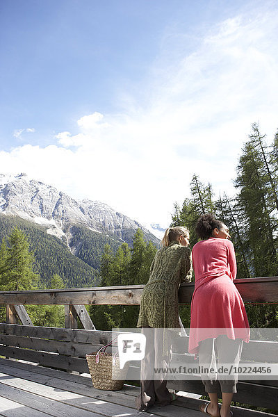 Switzerland  two young women standing on terrace looking at view