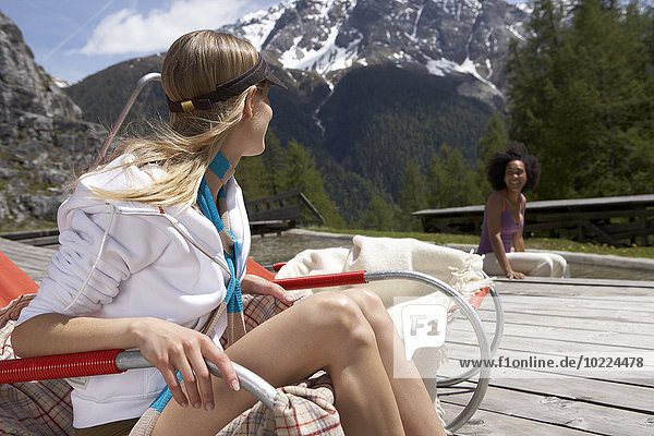 Switzerland  two young women relaxing on a sun deck